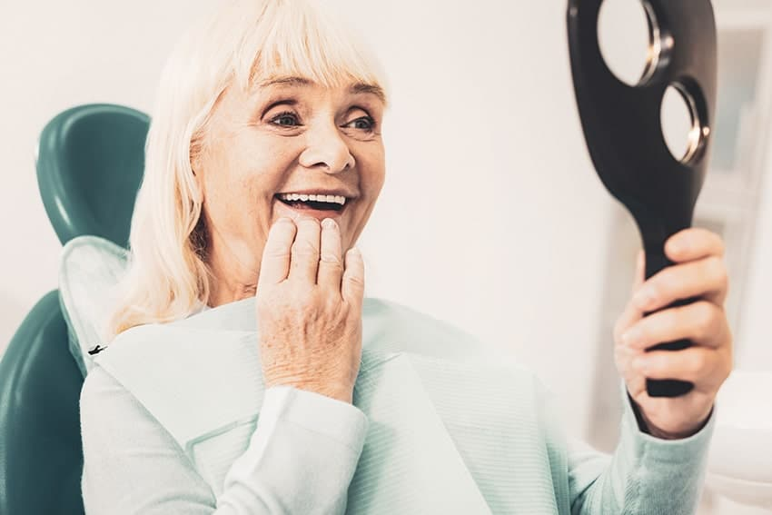 Excited older woman amazed by her new denture alternatives