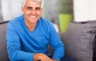 Mature man relaxes on his couch while relaxing