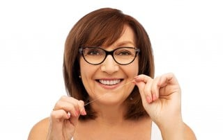 Mature woman stands smiling ready to floss her teeth