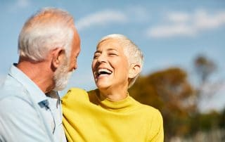 happy mature couple laughing while taking a walk outdoors