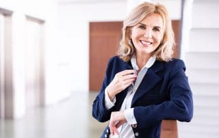 mature business woman leaning on a rail outside her office