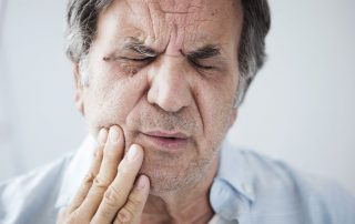 senior man with tooth and jaw pain